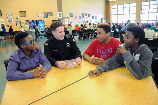 Dayton police officer Zach Hastings sits down to lunch with Belmont High  School students (from left) Seth Burdette, Kenyon Evans and Billy Veal ...