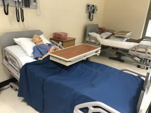 A mannequin sits in a hospital bed in an Allied Health classroom.