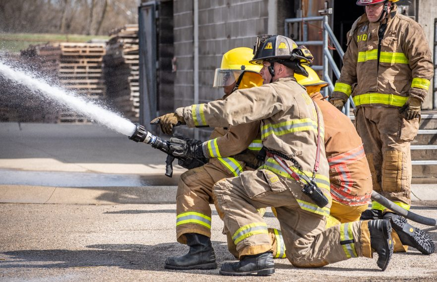 An instructor with the Dayton Fire Department teaches Belmont Fire students how to use a fire hose.