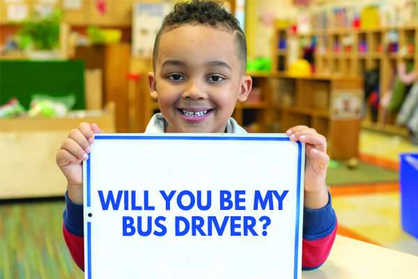 student holding bus driver sign